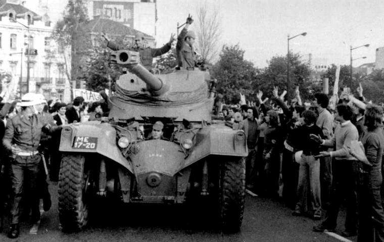 FILE - In this April 25 1974 file picture, people cheer soldiers in a tank driving through downtown Lisbon during a military coup.