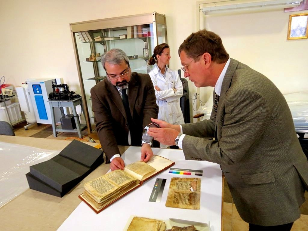 Francesco d'Aiuto, left, and the lead conservator Angela Nunez Gaitan, center, at the Vatican library displaying a leaf of the Syriac Galen Palimpsest as imaging team member Bill Christens-Barry, right, prepared for the work that makes it possible to read erased text.CreditR.B. Toth Associates
