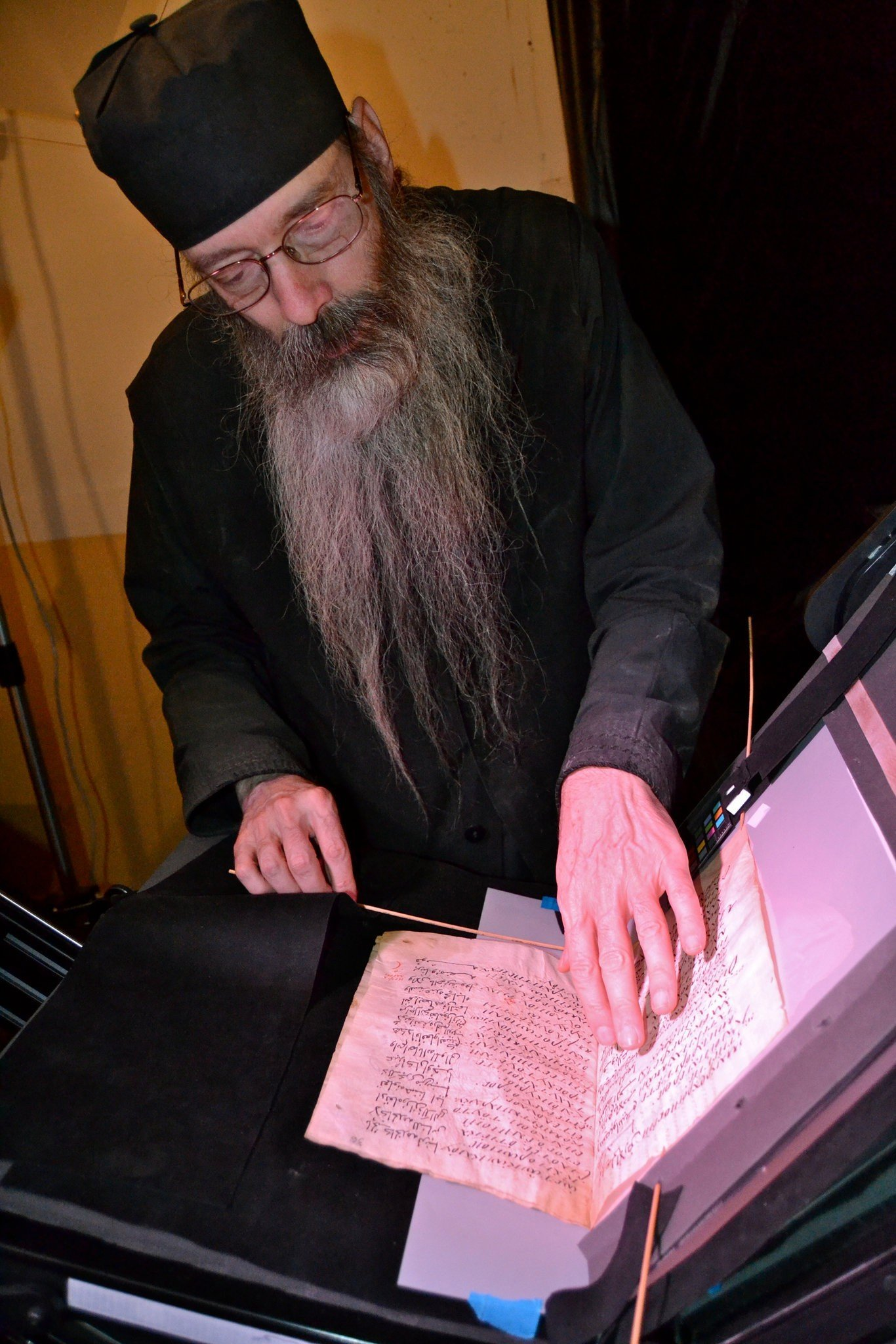 The librarian at St. Catherine's examining an ancient text.CreditMark Schrope